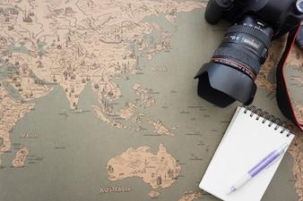 Fondo de mapa del mundo vintage con cuaderno, cámara y bolígrafo