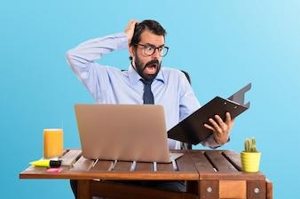Frustrado empresario en su oficina con su carpeta sobre fondo de colores