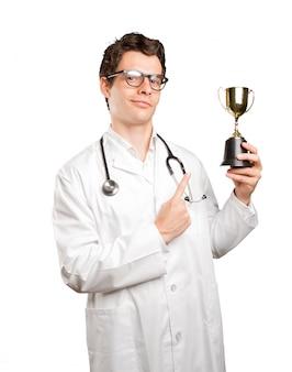 Ganador médico con una taza de oro contra el fondo blanco