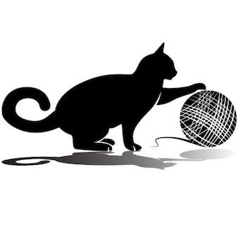 Gato negro que juega con la bola de lana