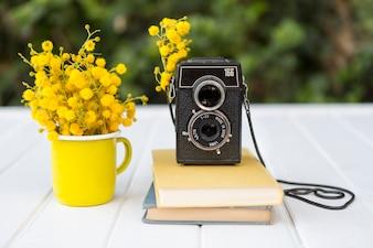 Genial composición con flores, cámara retro y libros