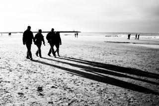 Gente caminando en la playa de arena blanca