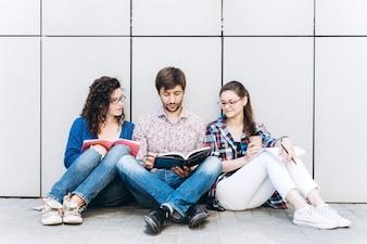 Gente con libros y gadgets sentado en el suelo cerca de la pared. Concepto de medios sociales de educación.