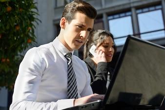 Gente de negocios ocupada trabajando al aire libre