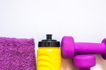 Gimnasio equipos de gimnasio. Pesas con la toalla y el embotellador del wate. Calzado de entrenamiento. Entrenadores deportivos sobre fondo blanco. Deporte, estilo de vida saludable y objetos concepto