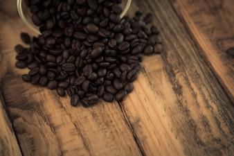 Granos de café sobre una mesa de madera saliendo de un bol