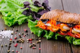 Granos de pimienta, la sal y el verdor se encuentran antes sándwich sano integral