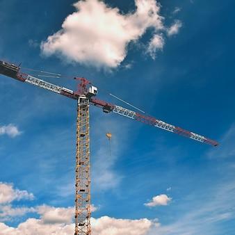 Grúa en la construcción con nubes de cielo azul y el sol en el fondo.