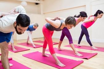 Grupo de personas que realizan ejercicio de yoga pose pirámide