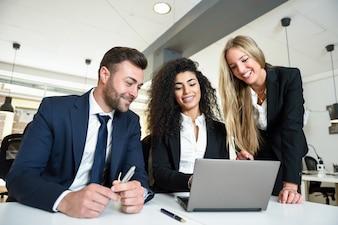 Grupo multiétnico de tres empresarios reunión en una oficina moderna. Dos mujeres y un hombre llevando traje mirando un ordenador portátil.