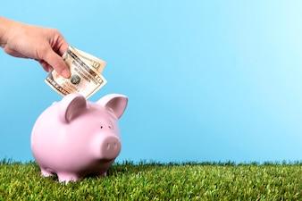 Guardando dinero en la hucha de cerdito