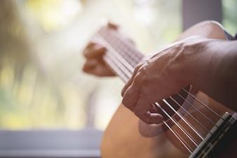Guitarrista de la guitarra acústica que juega. Instrumento musical con las manos del ejecutante