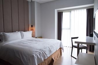 Habitación del hotel con cama doble, mesa y televisor