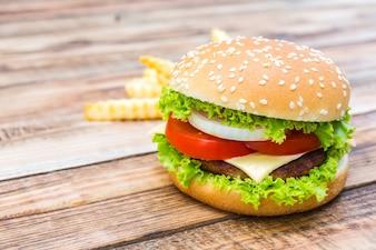 Hamburguesa apetitosa con patatas fritas de fondo