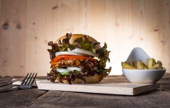Hamburguesa casera de pollo con papas fritas, lechuga, tomate y cebolla en tabla de madera.