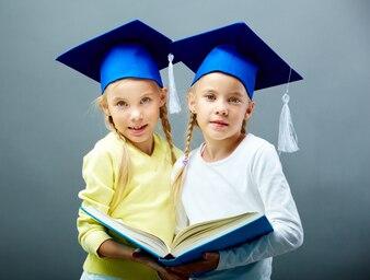 Hermanas con gorros de graduación compartiendo un libro