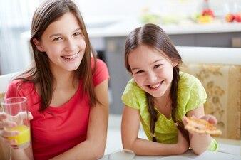 Hermanas disfrutando de pizza y zumo de naranja