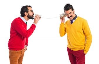 Hermanos gemelos hablando a través de un teléfono de hojalata