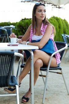 Hermosa chica con café en la calle.