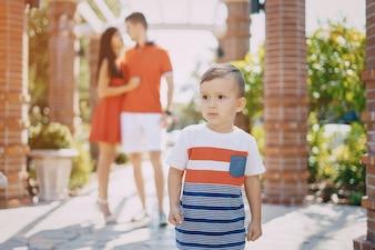 Hermosa familia en rojo caminando por la calle y el Parque