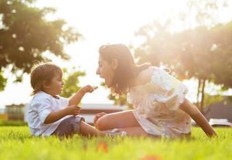 Hermosa joven madre con su hijo comiendo yogur en el parque.