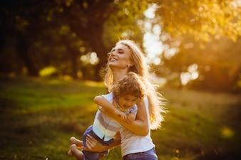 Hermosa joven madre con su hijo se divierten en un parque