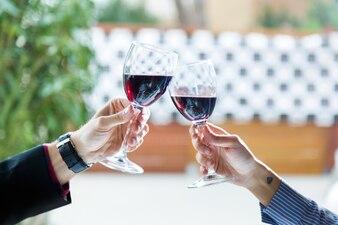Hermosa joven pareja tostado vasos de vino en el restaurante.