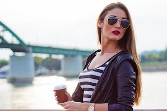 Hermosa mujer de negocios ocasional, chica con café en la puesta de sol río.