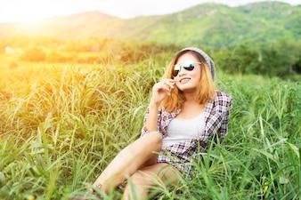 Hermosa mujer inconformista sentada en una pradera con la naturaleza y Moun