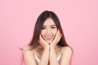 Hermosa mujer joven asiática sonriendo y tocar su rostro como una v-forma aislada sobre fondo de color rosa. Limpieza de la cara, piel perfecta. Terapia SPA, cuidado de la piel, cosmetología y cirugía plástica