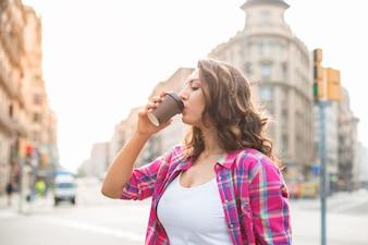 Hermosa mujer joven beber café en la calle