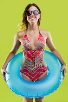 Hermosa mujer joven en bikini jugando con flotador. Aislado en verde.