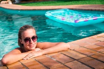 Hermosa mujer natural sonriendo en la piscina en vacaciones de verano. Joven modelo femenino en bikini.