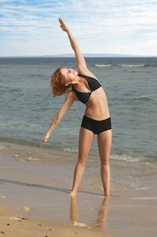Hermosa mujer roja de ejercicio en la playa