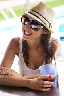 Hermosa niña bebiendo en el bar de la piscina.