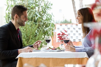 Hermosa pareja joven comiendo ensalada en el restaurante.