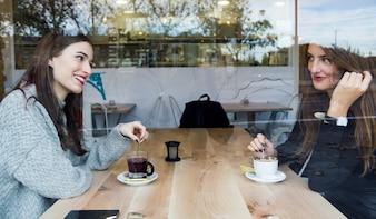 Hermosas mujeres jóvenes bebiendo té en una cafetería.