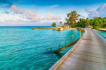 Hermosas villas de agua en la isla tropical de Maldivas en el momento de la salida del sol