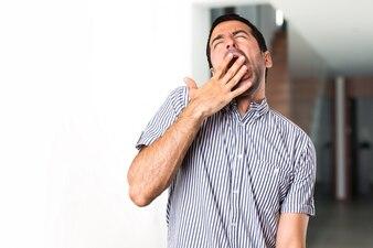 Hermoso hombre bostezando dentro de la casa