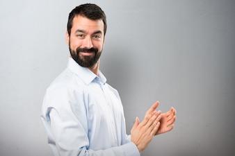Hermoso hombre con barba aplaudiendo sobre fondo de textura