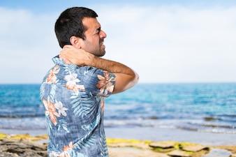 Hermoso hombre con camisa de flor con dolor de cuello en la playa