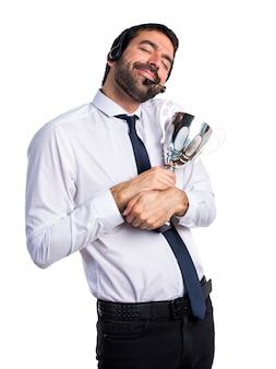 Hermoso hombre de telemercadeo sosteniendo un trofeo