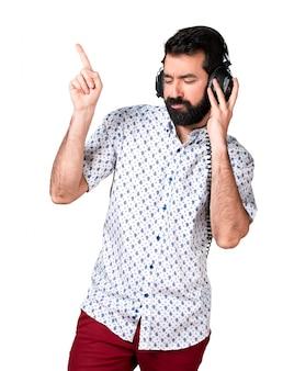 Hermoso hombre morena con barba escuchando música