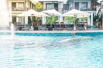Hermoso hotel de lujo piscina piscina con sombrilla y silla