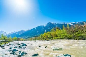 Hermoso río y las montañas cubiertas de nieve del paisaje Estado de Cachemira, India
