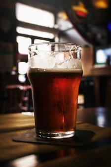 Hermoso vaso de cerveza fría sabrosa oscura en la barra. Fondo Oscuro.