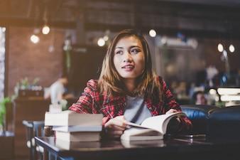 Hipster mujer adolescente sentado disfrutar de leer el libro en el café. Filtro Vintage en tonos.