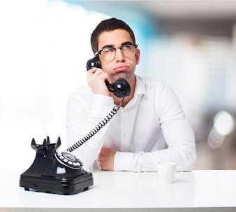 Hombre aburrido hablando por un teléfono negro