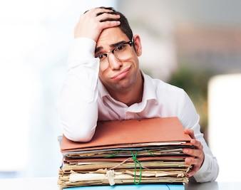 Hombre agobiado mirando un montón de papeles con una mano en la frente