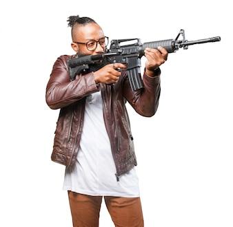 Hombre apuntando con la ametralladora a su lado